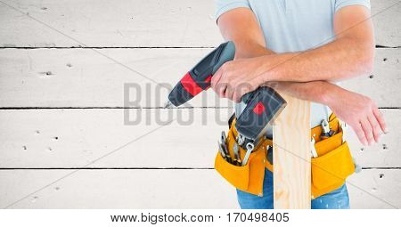 Mid section of handyman holding drill machine and plank against wooden background