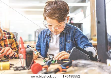 Serious boy absorbedly working with soldering iron at small mainboard