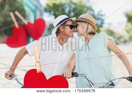 Composite image of happy couple rubbing nose with red hearts hanging on line