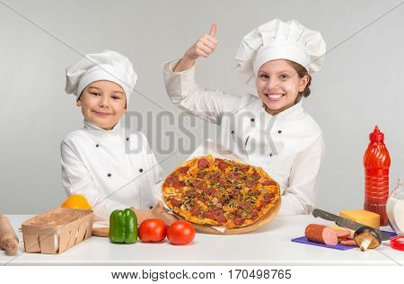 little boy and girl in white uniform of chef by the table with pizza