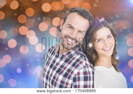 Close up of happy young couple standing back to back against glowing background