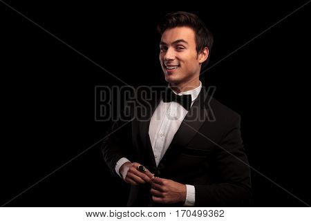 laughing young elegant man buttoning his tuxedo on black studio background