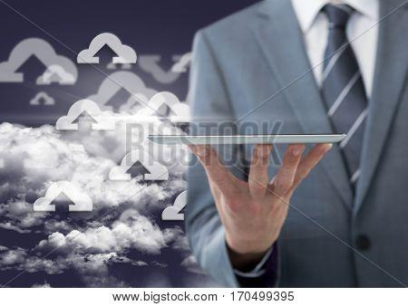 Digital composite image of businessman holding digital tablet against sky background