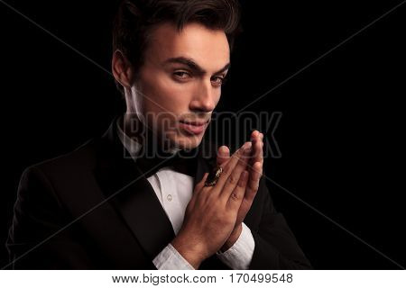 elegant man in tuxedo wearing big ring rubbing his palms together on black studio background