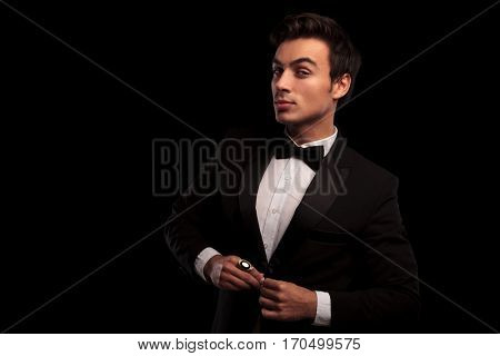 cool elegant young man in tuxedo unbuttoning his coat on black studio background
