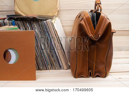 Retro styled image of a collection of old vinyl record lp's with sleeves on a wooden background. Copy space.