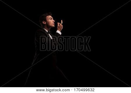 side view of an elegant man in tuxedo snapping his fingers and looks up to something on black studio background