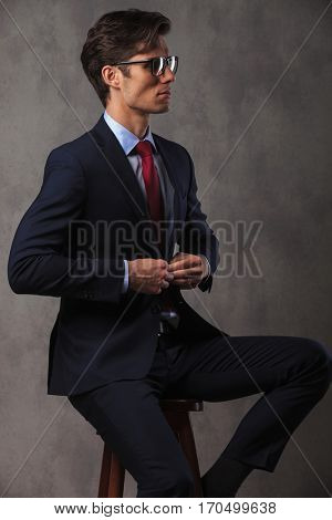 side view of an elegant business man buttoning his suit while sitting  in studio
