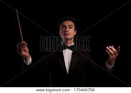 young elegant conductor directing his orchestra band on black studio background
