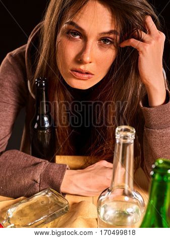 Woman alcoholism is social problem. Female drinking is cause of poor health. She drinking alcohol in bad mood and looking camera. Black background as symbol of mourning.