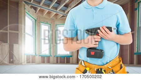 Mid section of handyman with tool belt and drill machine at workshop