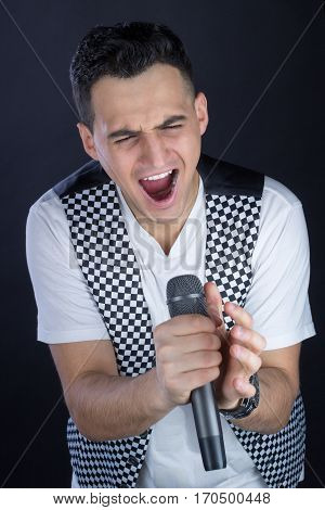 Male Black-haired Rock Singer Performs Singing To Microphone