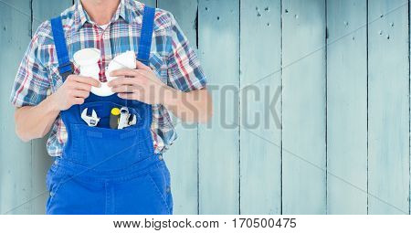 Mid section of handy man with tools standing against wooden background