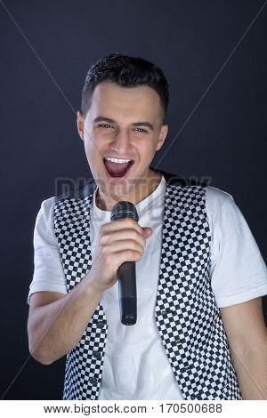Young Male Black-haired Rock Vocalist Performs Singing To Microphone