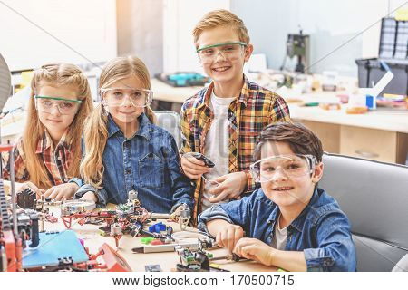 Hilarious children are in light workshop near table with details and drone. They looking directly at camera