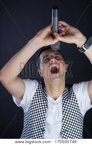Young Male Black-haired Pop Vocalist Performs Singing To Microphone