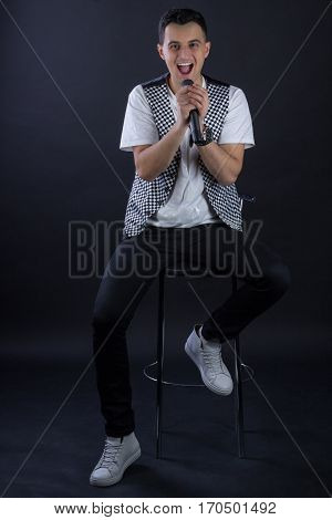 Young Male Black-haired Singer Posing Singing To Microphone