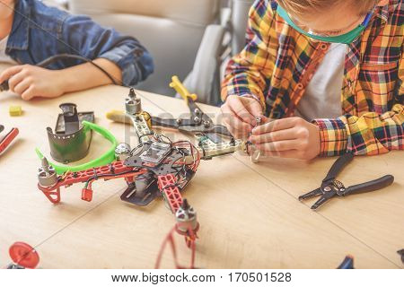 Concentrated children are sitting at desk. They compiling flying drone
