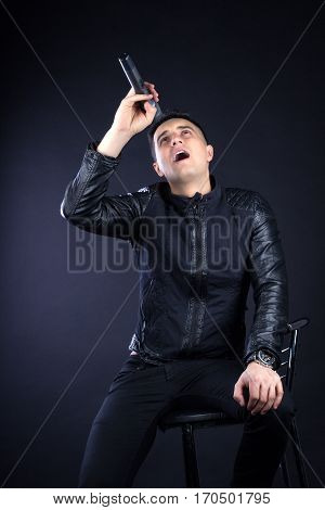 Young Male Black-haired Pop Singer Sings To Microphone