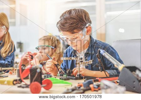 Concentrated boy is sitting near table. He looking at mainboard through loupe and using soldering iron