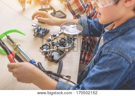 Smart young technician is sitting near desk. He holding pliers and looking at mainboard