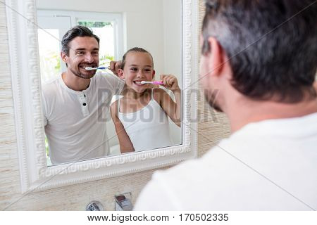 Father and daughter brushing their teeth in the bathroom