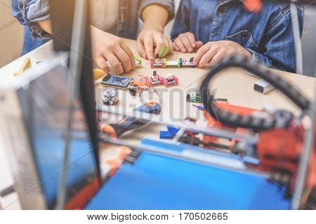 Children are near wooden desk. They compiling small spare parts. Focus on 3d printer