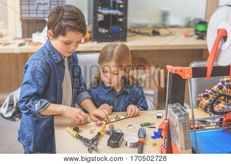 Concentrated boy is standing beside girl. She carefully watching how he compiling small details of mechanism