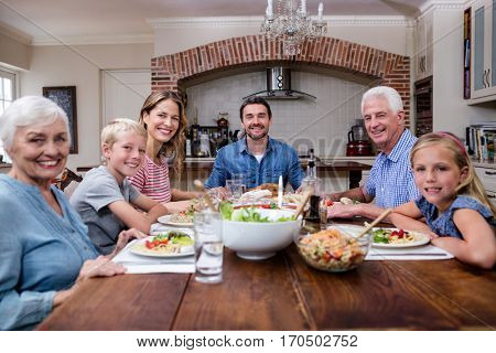 Multi-generation family having meal in kitchen at home