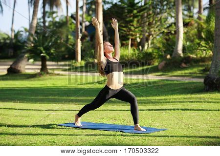 Attractive woman practices yoga in nature. Stock image.