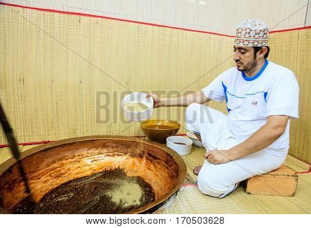 NIZWA, OMAN, MAY 27, 2016: factory worker adding ingredients to a kettle for making of traditional Omani halwa