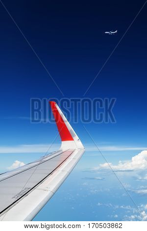 Oncoming flight traffic in mid air. Aircraft flying above beautiful earth clouds. Aerial view of clear blue sky aircraft wing from cabin through plane window. Travel tour background with copy space