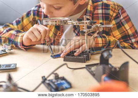 Serious boy is sitting near wooden table. He looking at main board through loupe