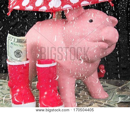 pink piggy bank with money in red boots and polka dot umbrella in rainy window