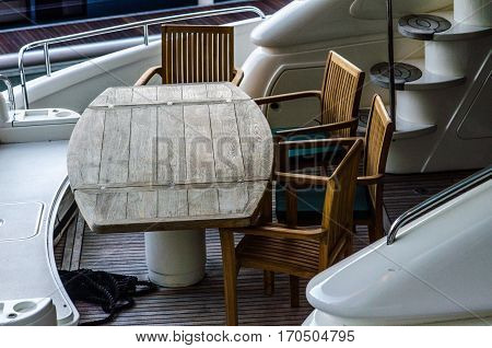 wooden table and chairs at the stern of a large ship anchored in port water