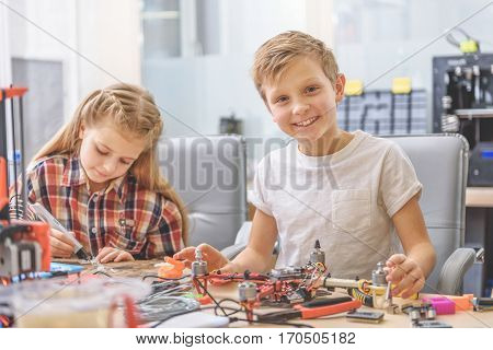 Hilarious boy is sitting beside busy girl near table, full of equipment. He looking at camera