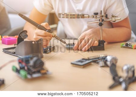 Young technician is using soldering iron for work at mainboard
