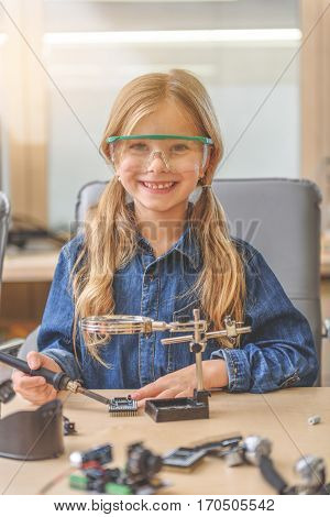Joyful girl is sitting near wooden desk, full of details. She holding soldering iron