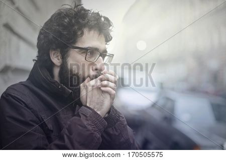 Man trying to warm his hands up by blowing them