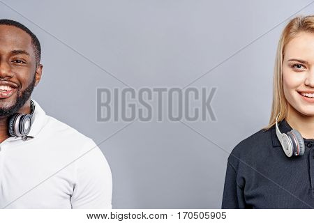 Happy young african man and European woman are standing and smiling. They are carrying headphones on neck. Vertical half of their portraits. Isolated on grey background and copy space