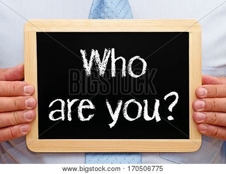 Who are you - Businessman holding chalkboard with text