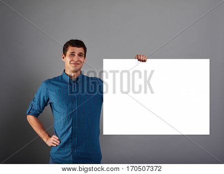 Smiling marketing manager holds big white poster in one hand. Happy man with blank paper list. Guy with copy space bord for advertising text or product.