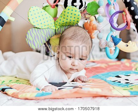 baby lying on Developing rug. playing in Mobile. educational toys. Sweet child Crawling And Playing With Toys On Carpet