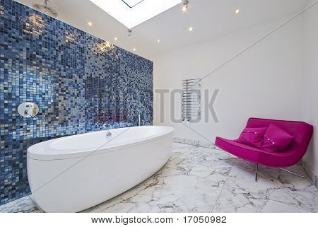 large modern porcelain bath and a magenta pink sofa
