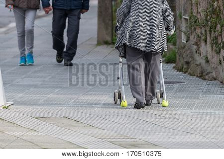 old woman with a device on wheels for a walk on the street