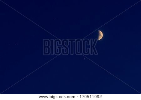 half moon and small stars on a blue night sky