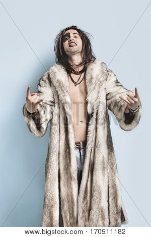 Portrait of young man in fur coat gesturing rock music sign against light blue background