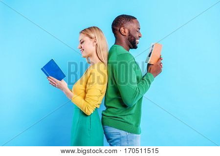 Carefree young couple is reading books with interest. They are standing while leaning back to each other and smiling. Isolated on blue background