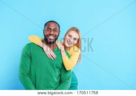 We are happy together. Carefree young man and woman are hugging with love. They are looking at camera and smiling. Isolated on blue background