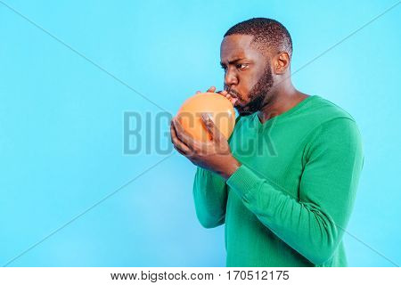 Serious young african man is inflating the balloon with concentration. Isolated on blue background. Copy space in left side